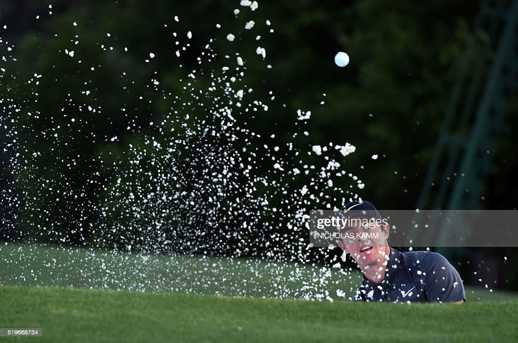 Northern Ireland's Rory McIlroy reacts after playing a shot out of a bunker on the 18th green during Round 1 of the 80th Masters Golf Tournament at...