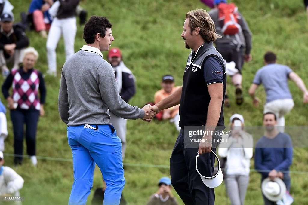 Northern Ireland's Rory McIlroy (L) shakes hands with France's Victor Dubuisson (R) on the 9th green during the first round of the 100th French Golf Open on July 30, 2016 at Le Golf National in Guyancourt, near Paris. / AFP / DOMINIQUE