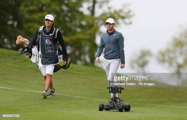 Northern Ireland's Rory McIlroy with caddy Harry Diamond walk past a remote controlled camera on the course