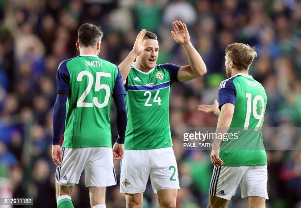 Northern Ireland's striker Conor Washington celebrates with Northern Ireland's defender Michael Smith and Northern Ireland's striker Jamie Ward after...