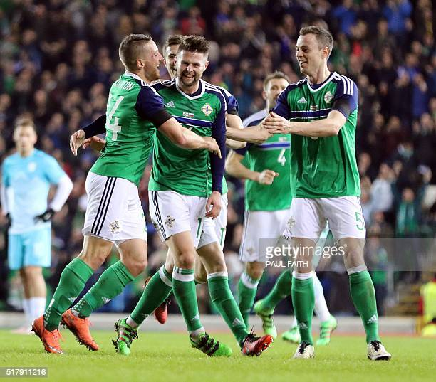 Northern Ireland's striker Conor Washington celebrates with teammates after scoring the opening goal of the international friendly football match...