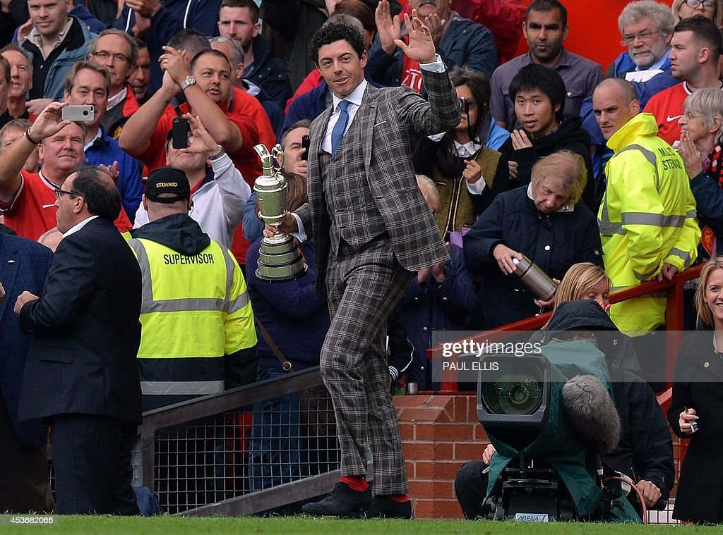 Northern Irish golfer Rory McIlroy appears at half time with his British open golf trophy during the English Premier League football match between Manchester United and Swansea City at Old Trafford in Manchester, north west England on August 16, 2014. Swansea City won the game 2-1.