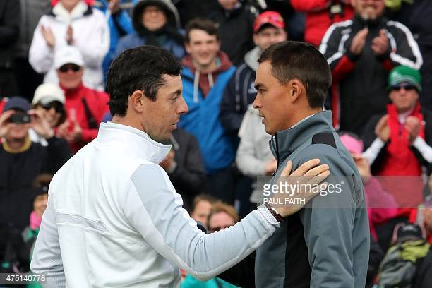 Northern Irish golfer Rory McIlroy shakes hands with US golfer Rickie Fowler after finishing on the 18th green on the second day of the Irish Open at...