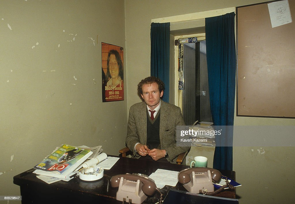 Northern Irish politician Martin McGuinness sits behind his desk in the Republican Information Centre office in Londonderry with a poster of Bobby Sands, the famous hunger striker, on the wall behind him, 23th September 1985. An alleged IRA leader, he became deputy First Minister of Northern Ireland in 2007.