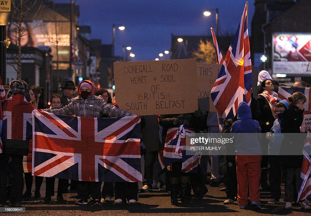 Northern Irish protesters hold the union flag as they block the Donegall road in Belfast, Northern Ireland, on December 11, 2012 amid renewed tensions after Belfast city councillors voted not to fly the British flag all year around. Around 3,500 people were killed in the three decades of sectarian bloodshed between Northern Irish Protestants favouring continued union with Britain, and Catholics seeking a unified Ireland. AFP PHOTO/ PETER MUHLY