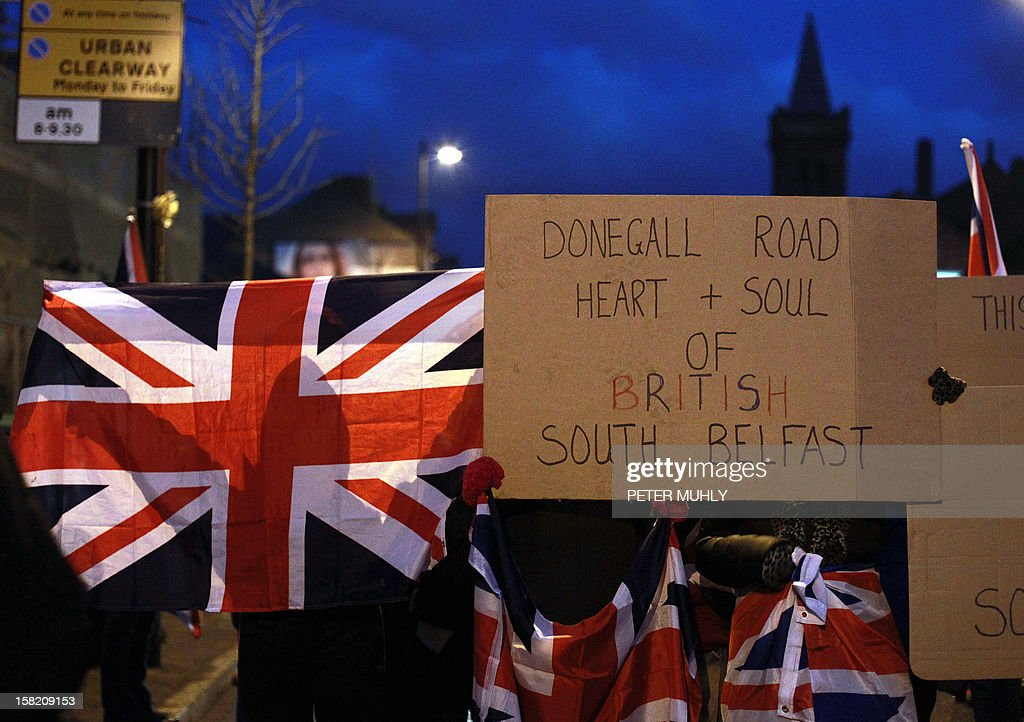 Northern Irish protesters hold the union flag as they block the Donegall road in Belfast, Northern Ireland, on December 11, 2012 amid renewed tensions after Belfast city councillors voted not to fly the British flag all year around. Around 3,500 people were killed in the three decades of sectarian bloodshed between Northern Irish Protestants favouring continued union with Britain, and Catholics seeking a unified Ireland.