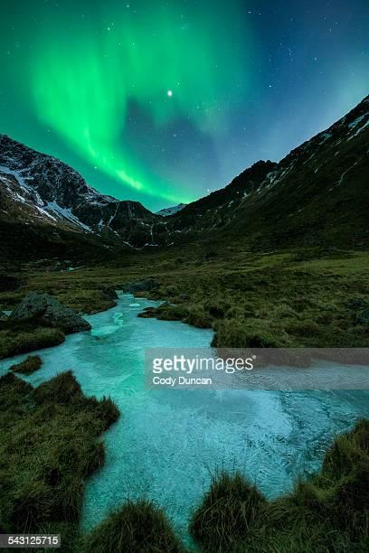 Northern Lights - Aurora Borealis shine in sky over frozen ice river and mountain landscape, Flakstadoy, Lofoten Islands, Norway