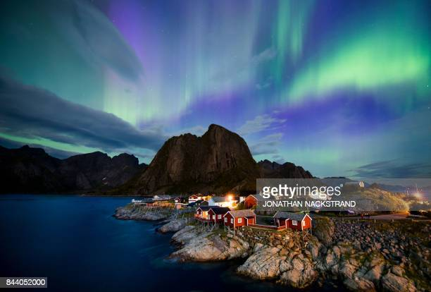 Northern lights illuminate the sky over Reinfjorden in Reine on Lofoten Islands Arctic Circle on September 8 2017 / AFP PHOTO / Jonathan NACKSTRAND