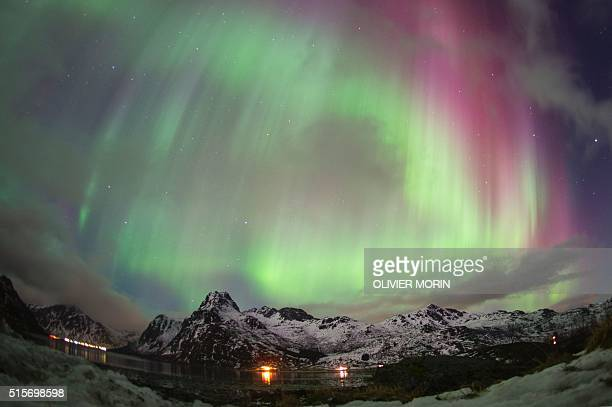 Northern lights illuminate the sky over the snow covered Fjord of Flakstad on Lofoten Islands Arctic Circle on March 14 2016 Surfers from all over...