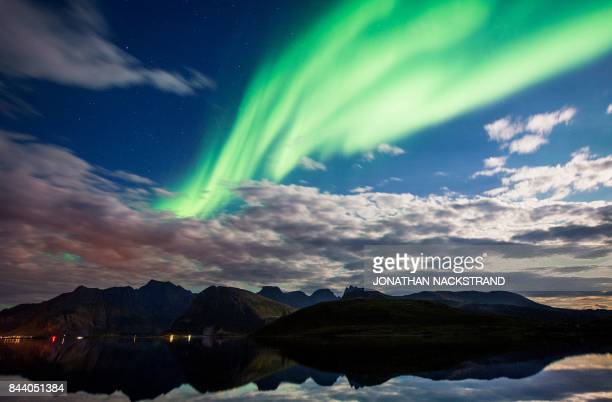 TOPSHOT Northern lights illuminate the sky over Torsfjorden near Reine on Lofoten Islands Arctic Circle on September 8 2017 / AFP PHOTO / Jonathan...