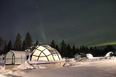 Northern Lights (Aurora Borealis) dancing above Glass Igloos in Lapland, Finland.
