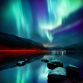 A large Northern Lights (aurora borealis) display glowing over a mountain pass and reflected on a lake at night. Photo composition.