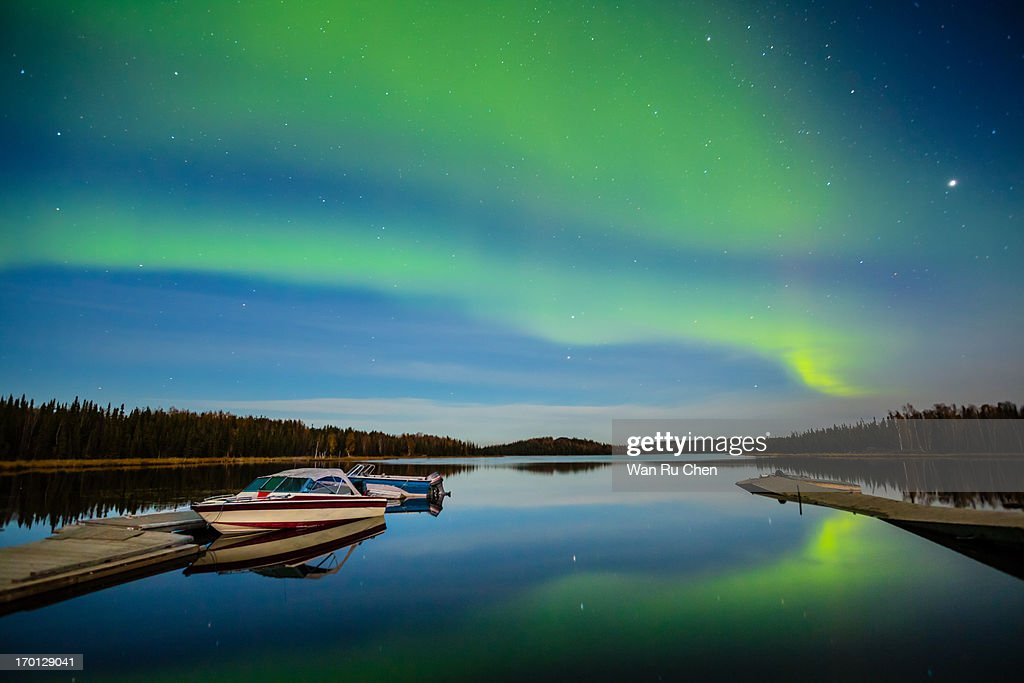 Northern lights reflection acros a lake