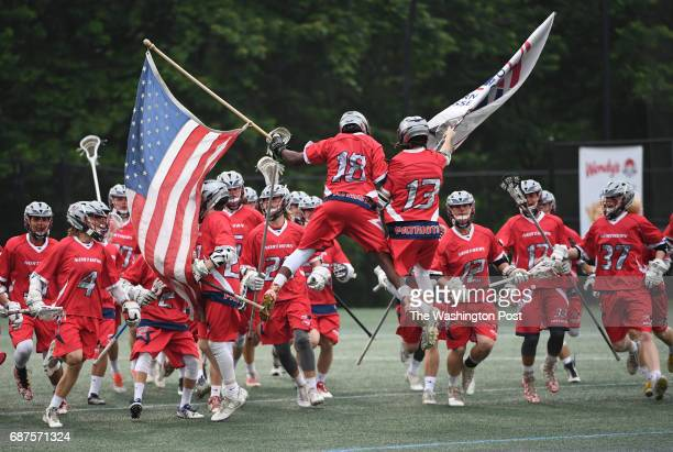 Northern players Darryl Walker and Colten King lead their team onto the field carrying the American and high school flags at the start of the...