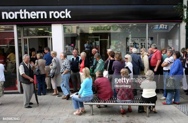 Northern Rock Plc bank customers stand in line and sit on a bench as they wait outside the bank to withdraw their savings at a branch in...