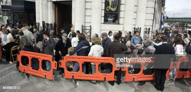 Northern Rock Plc customers stand in line outside the bank as they wait to withdraw their savings at a branch in Golders Green London UK on Monday...
