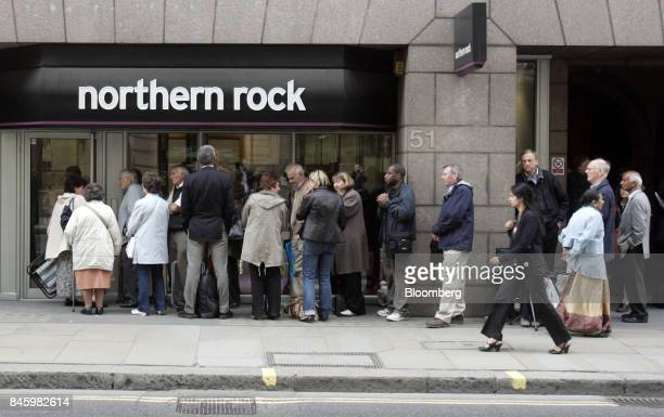 Northern Rock Plc customers stand in line outside the bank as they wait to withdraw their savings at a branch in Moorgate London UK on Monday Sept 17...
