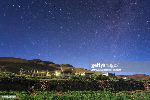 Northern stars above a moonlit Tibetan village in Tibet, China.
