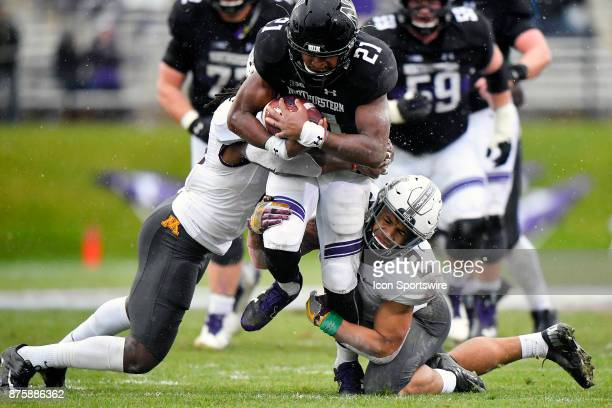Northwestern Wildcats running back Justin Jackson is tackled by Minnesota Golden Gophers defensive back Duke McGhee and Minnesota Golden Gophers...