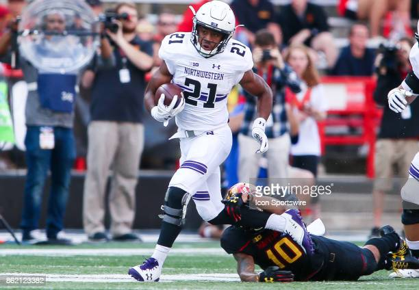 Northwestern Wildcats running back Justin Jackson runs past Maryland Terrapins defensive back Josh Woods during a college football game between the...