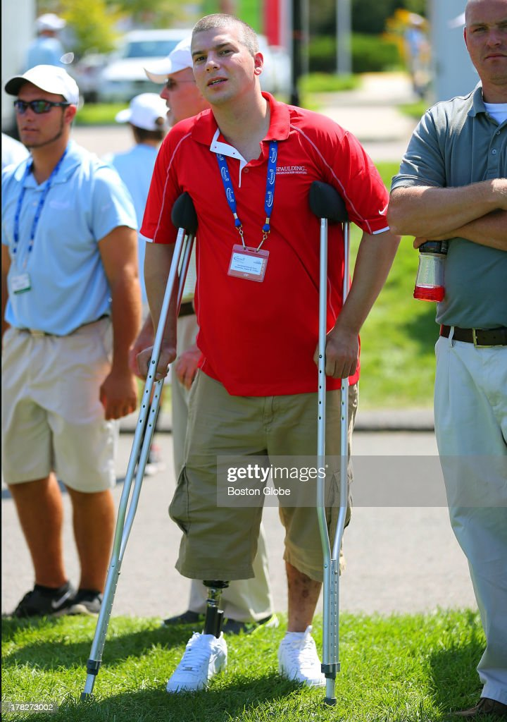 J.P. Norton, who lost a leg in the Boston Marathon bombings watches golfers at the driving range. Norton earlier received golf clubs from Nike as part of a program with Spaulding Hospital and Golfsmith to help marathon survivors get out on the links. Practice took place at the TPC Boston for the Deutsche Bank Championship, Aug. 28, 2013.