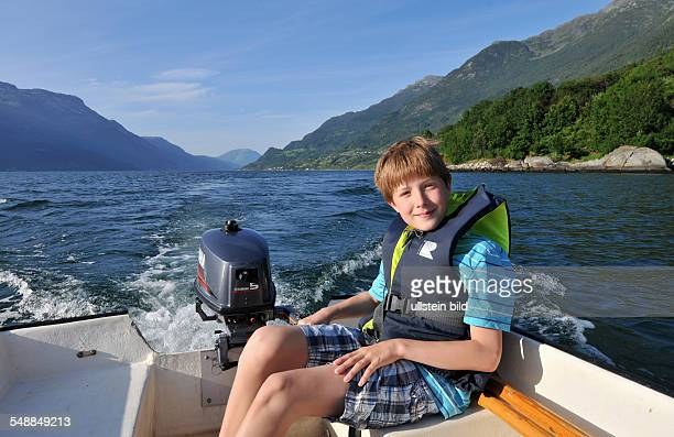 Norway boy with a life jacket is driving a motor boat on the Soerfjord
