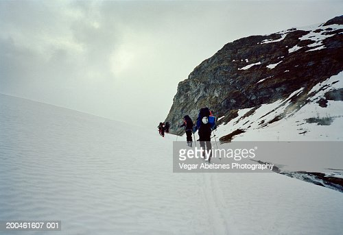 Norway, Jotunheimen, group Randonee skiing in single file, rear view : Bildbanksbilder