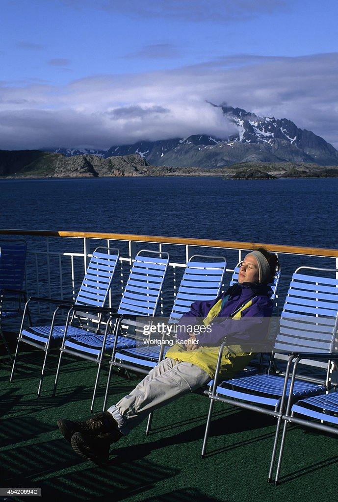 Norway, Lofoten Islands, Near Svolvaer, Coastal Express Ship Ms Kong Harald, Passenger Sunbathing On Deck.
