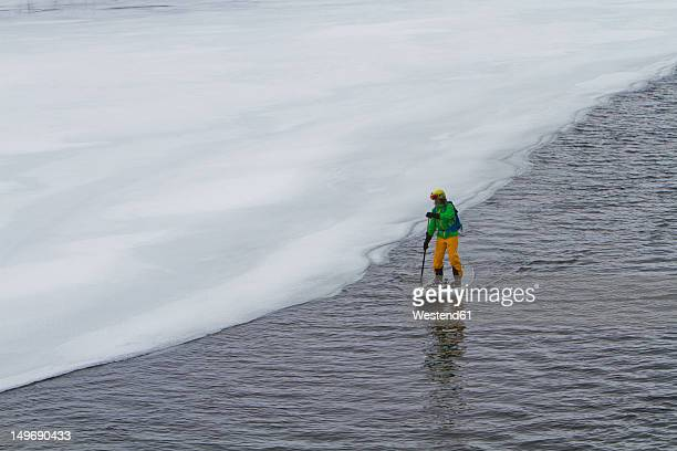 Norway, Narvik, Mature man paddling in polar ocean