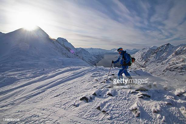Norway, Skier walking in snow with pole