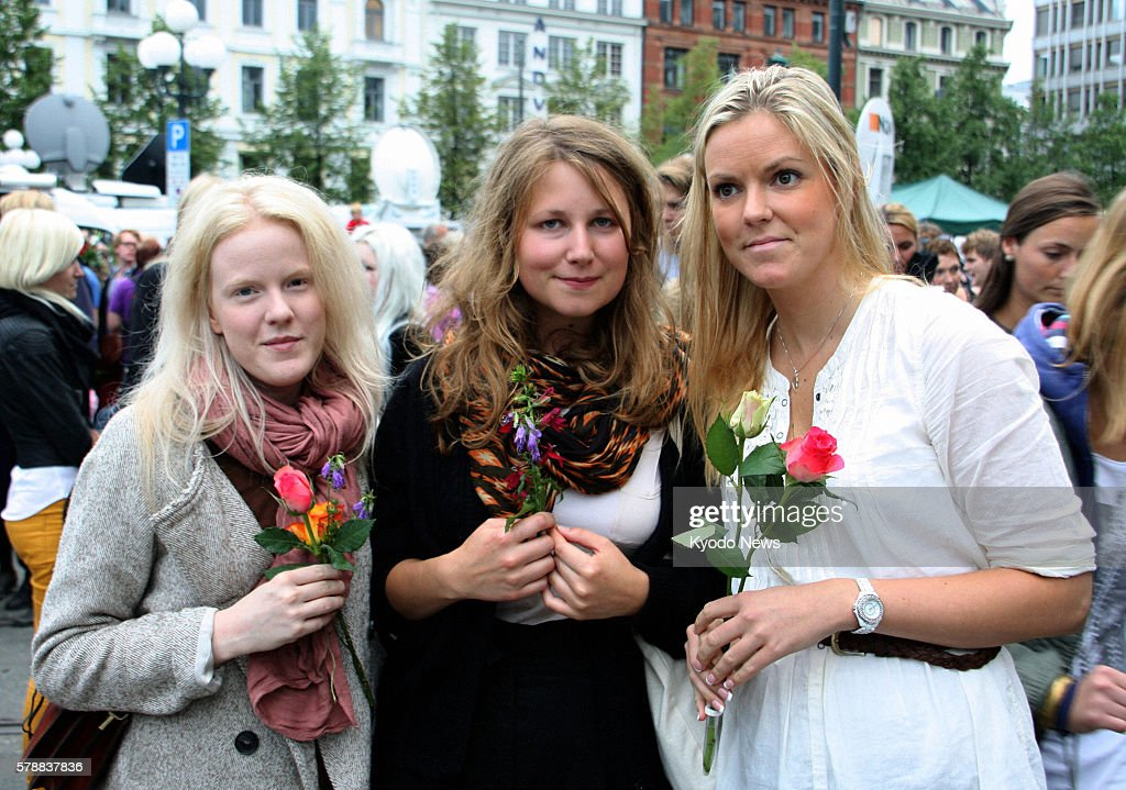 OSLO Norway Women carry flowers to a gathering near a cathedral in Oslo on July 25 to mourn for the dozens of victims of attacks by a man in Oslo and...