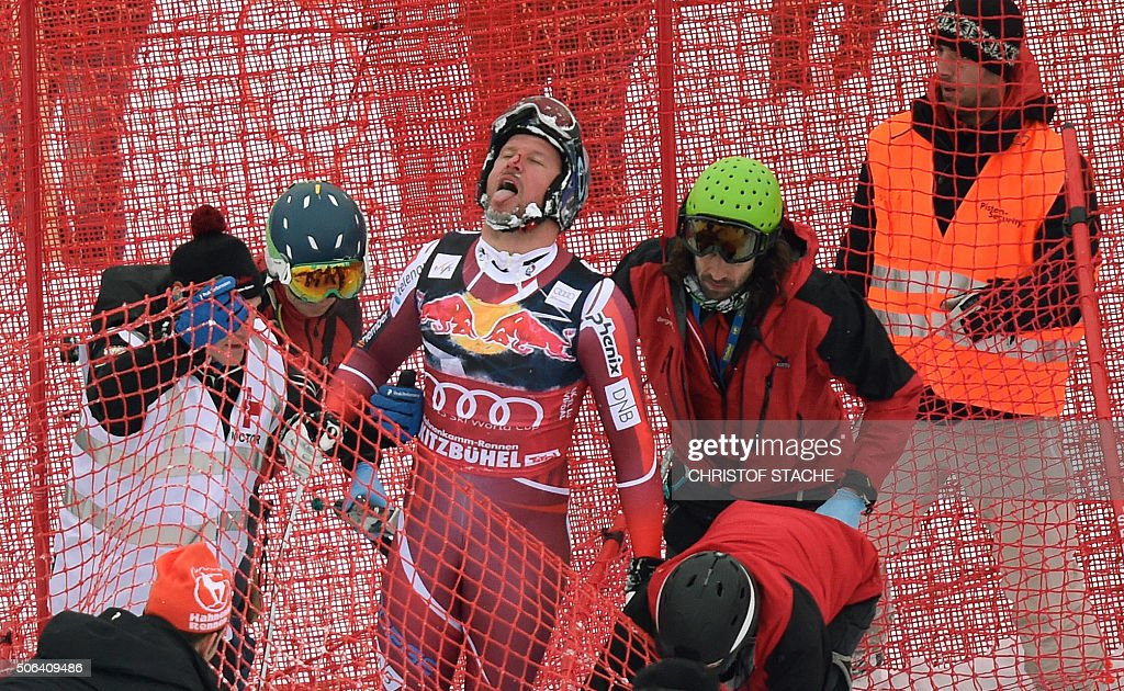 Norway's Aksel Lund Svindal is helped by medical staff after crashing during the Audi FIS Alpine Ski World Cup Men's Downhill on January 23 2016 in...