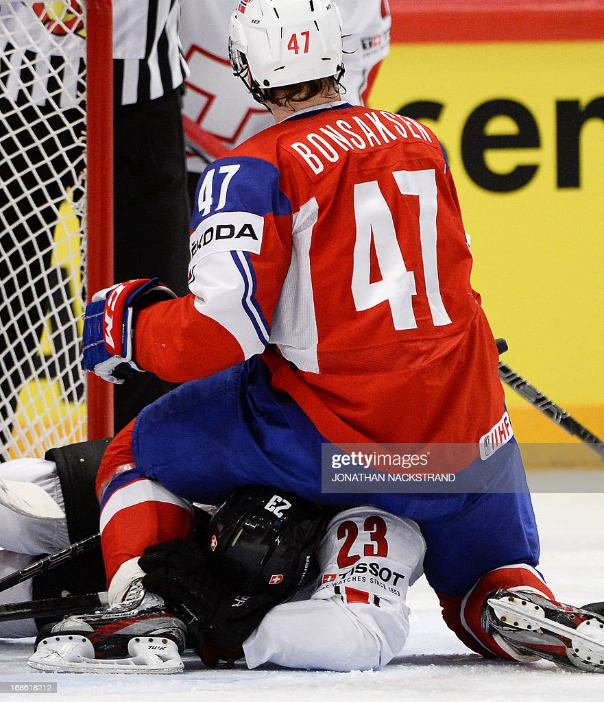 Norway's Alexander Bonsaksen (front) sits on Switzerland's Simon Bodenmann during the preliminary round match Norway vs Switzerland at the 2013 IIHF Ice Hockey World Championships on May 12, 2013 in Stockholm.
