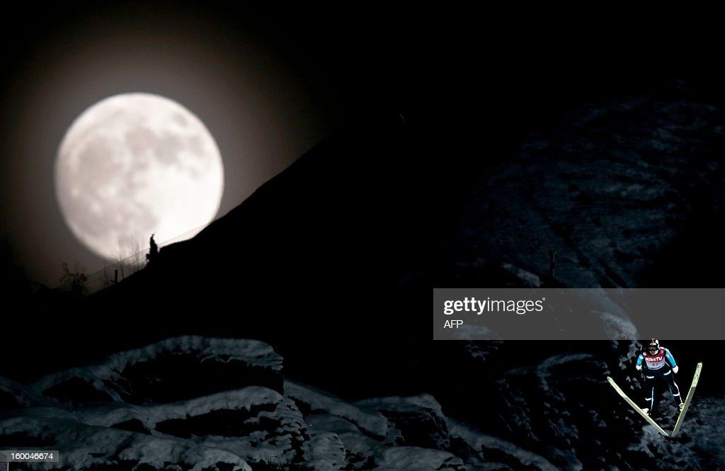 Norway's Anders Bardal jumps during the official training session of the FIS Ski Flying World Cup in Vikersund, Norway on January 25, 2013, while a full moon rises over the mountain.
