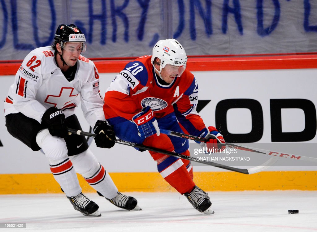 Norway's Anders Bastiansen (R)and Switzerland's Simon Moser vie for the puck during the preliminary round match Norway vs Switzerland at the 2013 IIHF Ice Hockey World Championships on May 12, 2013 in Stockholm.
