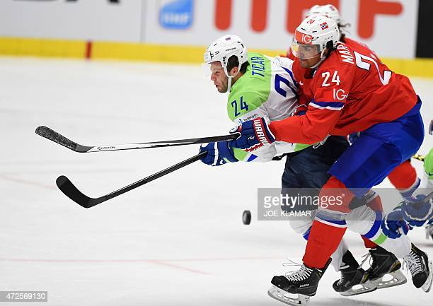 Norway's Andreas Martinsen and Slovenia's Rok Ticar vie for the puck during the group B preliminary round match between Slovenia and Norway during...