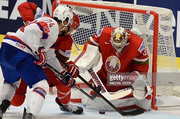 Norway's Andreas Martinsen fights for the puck with Nikolai Stasenko of Belarus and Belarussian goalkeeper Vitali Koval during the group B...