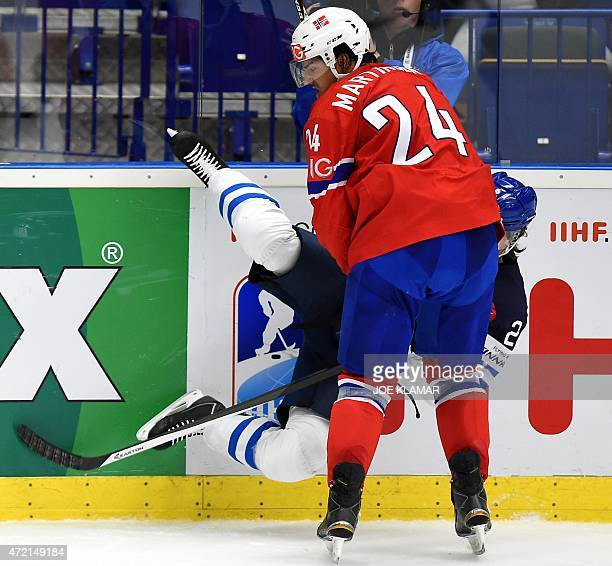 Norway's Andreas Martinsen hits Finland's Jyrki Jokipakka to the boards during the group B preliminary round ice hockey match Norway vs Finland of...