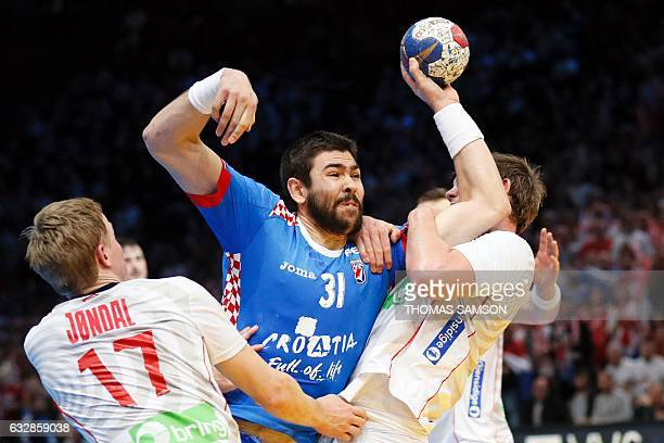 Norway's centre back Sander Sagosen and Norway's left wing Magnus Jondal hold back Croatia's right back Luka Sebetic during the 25th IHF Men's World...