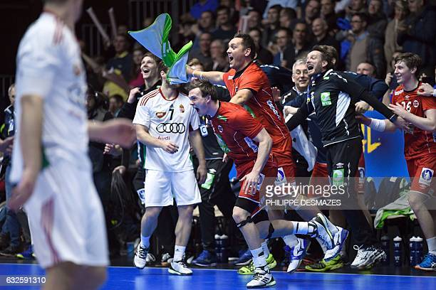 Norway's centre back Sander Sagosen Norway's pivot Joakim Hykkerud and Norway's head coach Christian Berge rush onto the court after Norway won the...