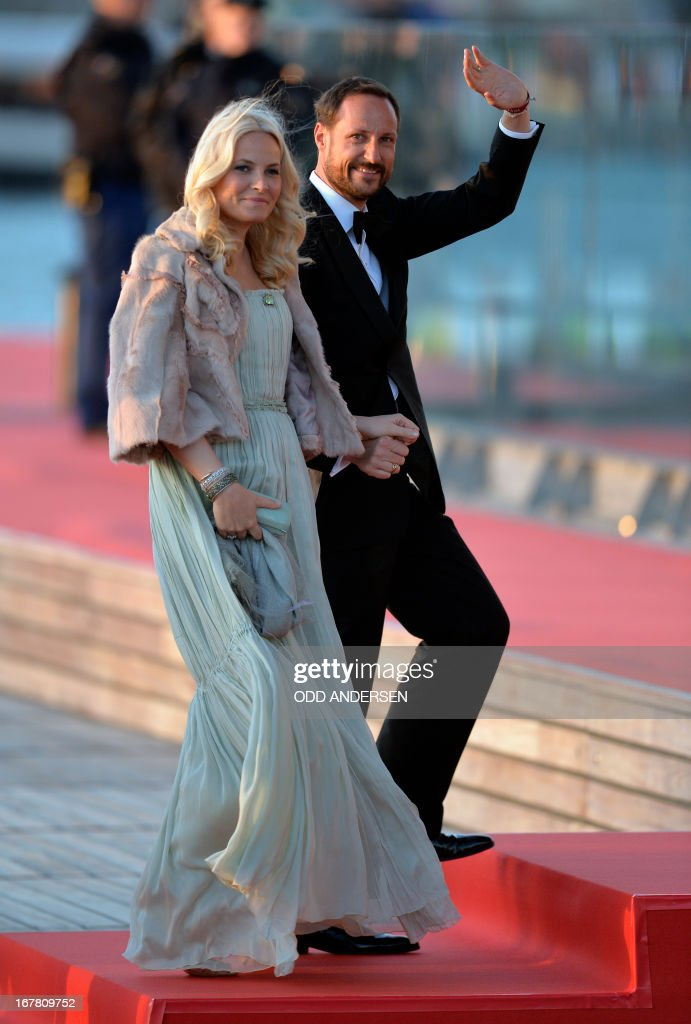 Norway's Crown Prince Haakon and Crown Princess Mette-Marit of Norway go toward a boat on April 30, 2013 to take part in a water pageant on the river IJ in Amsterdam on the day of the new King's investiture.
