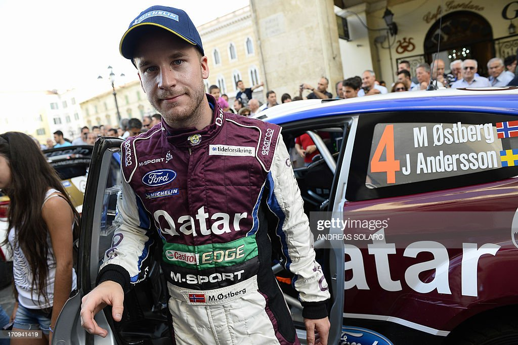 Norway's driver Mads Ostberg stands in front of his car, a Ford Fiesta RS WRC, during the opening ceremony of the FIA World Rally Championship of Italy in Sassari, on the Italian island of Sardinia on June 20, 2013.