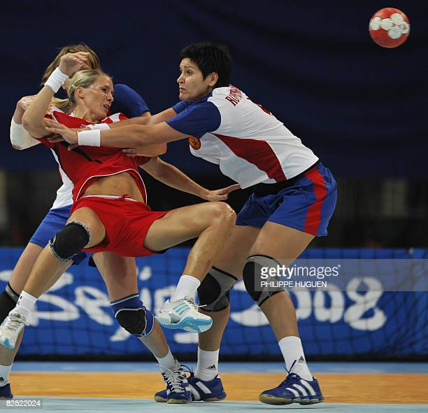 Norway's Gro Hammerseng is grabbed by Russia's Oxana Romenskaya during the women's handball gold medal match of the 2008 Beijing Olympic Games on...