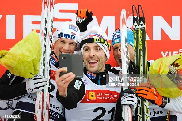 Norway's Magnus Moan takes a selfie with Norway's Magnus Krog and Austria's Bernhard Gruber on the podium of the skiing race during the individual...