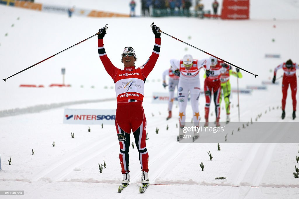 Norway's Marit Bjoergen celebrates on February 21, 2013 as she crosses the finish line of the Women's Cross Country skiing sprint final 1,2km race of the FIS Nordic World Ski Championships at Val Di Fiemme Cross Country stadium in Cavalese, northern Italy. AFP PHOTO / PIERRE TEYSSOT