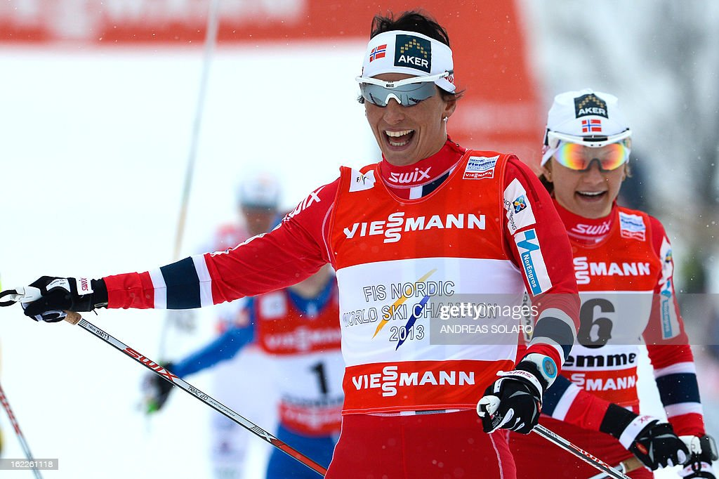 Norway's Marit Bjoergen (L) celebrates on February 21, 2013 as she crosses the finish line ahead of Maiken Caspersen Falla of Norway who finished third during the Women's Cross Country sprint final 1.2km race of the FIS Nordic World Ski Championships at Val Di Fiemme Cross Country stadium in Cavalese, northern Italy. Bjoergen finished first ahead of second place winner Ida Ingemarsdotter of Sweden and third place winner Maiken Caspersen Falla of Norway.