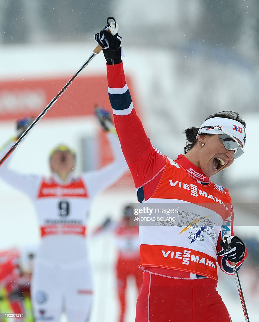 Norway's Marit Bjoergen celebrates on February 21, 2013 as she crosses the finish line during the Women's Cross Country sprint final 1.2km race of the FIS Nordic World Ski Championships at Val Di Fiemme Cross Country stadium in Cavalese, northern Italy. Bjoergen finished first ahead of second place winner Ida Ingemarsdotter of Sweden and third place winner Maiken Caspersen Falla of Norway.