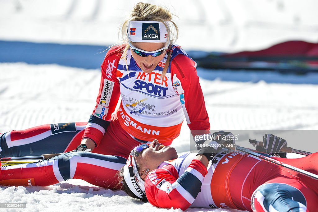 Norway's Marit Bjoergen (R) lies on the ground and speaks to Norway's Therese Johaug after coming in first place on March 2, 2013 at the Women's Cross Country 30 km Classic race of the FIS Nordic World Ski Championships at Val Di Fiemme Cross Country stadium in Cavalese, northern Italy.