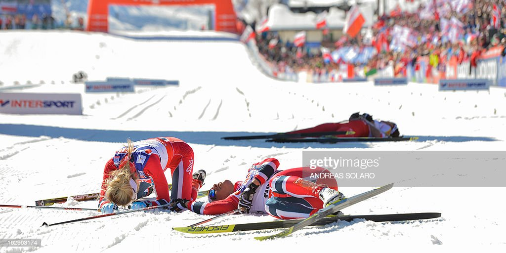 Norway's Marit Bjoergen (C) lies on the ground in the finish area next to Norway's Therese Johaug (L) and Poland's Justyna Kowalczyk, after coming in first at the Women's Cross Country 30 km Classic race of the FIS Nordic World Ski Championships on March 2, 2013 at Val Di Fiemme Cross Country stadium in Cavalese, northern Italy. AFP PHOTO / ANDREAS SOLARO