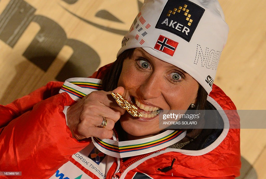 Norway's Marit Bjoergen poses with her gold medal on the podium at the medals ceremony of the Women's Cross Country 30 km Classic race of the FIS Nordic World Ski Championships at Val Di Fiemme Cross Country stadium in Cavalese, northern Italy, on March 2, 2013. AFP PHOTO / ANDREAS SOLARO